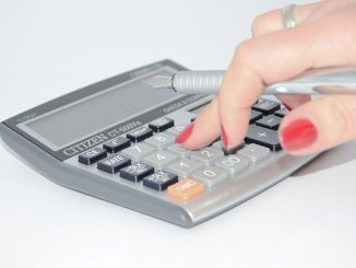 a lady's hand holding a pen and using a calculator