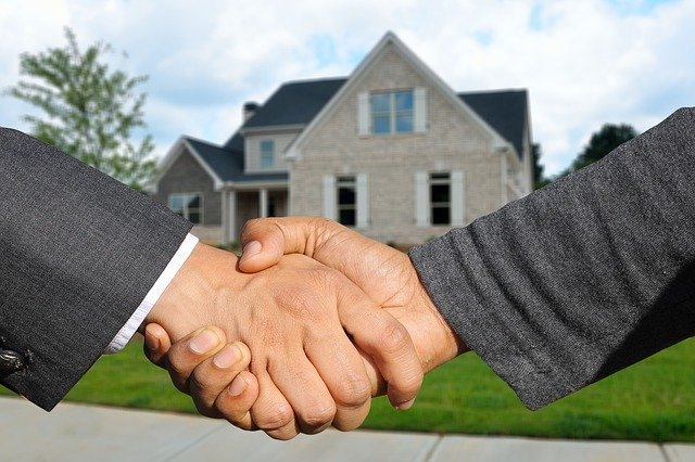 shaking hands infront of a house