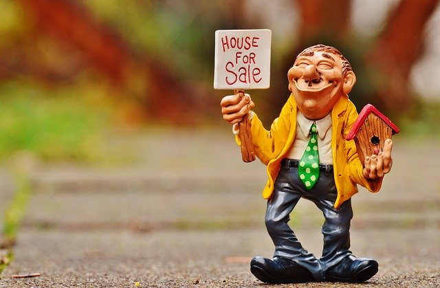 model of a man holding a house for sale sign