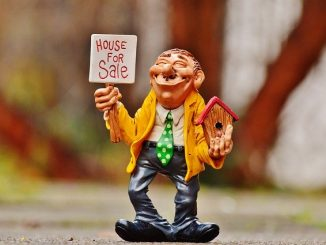 model of a man holding a for sale sign