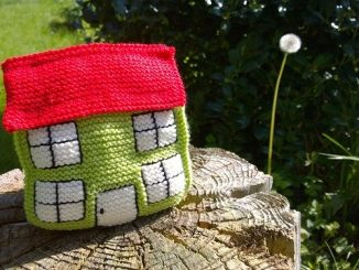 knitted house sat on a tree stump