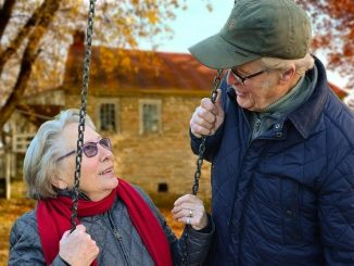 elderly couple, the lady is on a swing and there's a house in the background