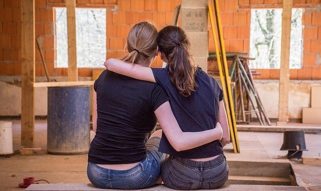 2 ladies with their arms around each other infront of a room which is being renovated