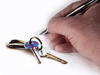 a hand with a fountain pen and some keys