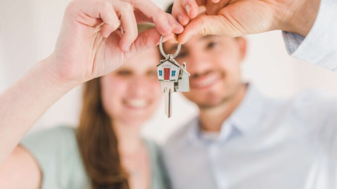 2 people holding a key